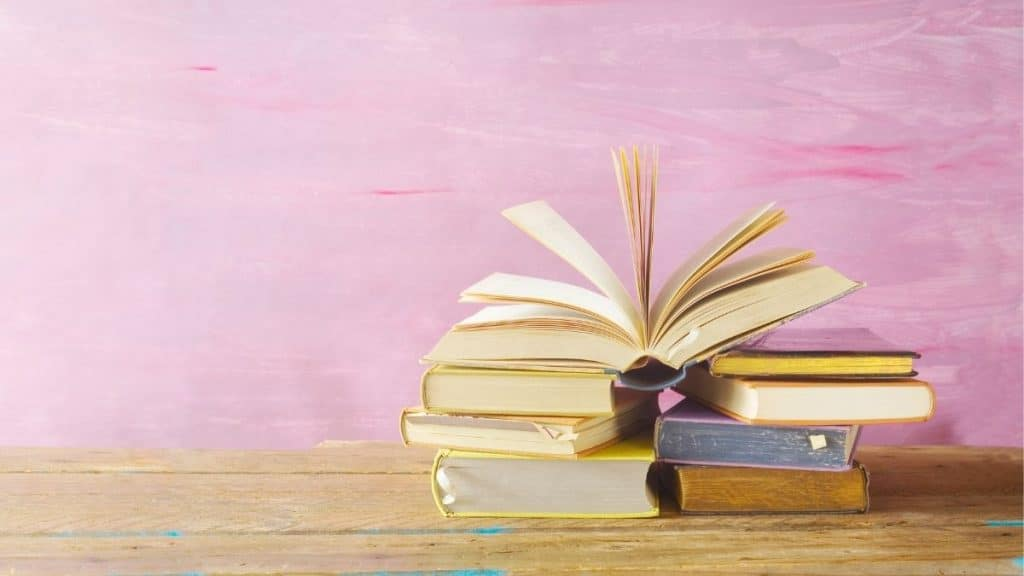 stack of books on brown table with pink wall