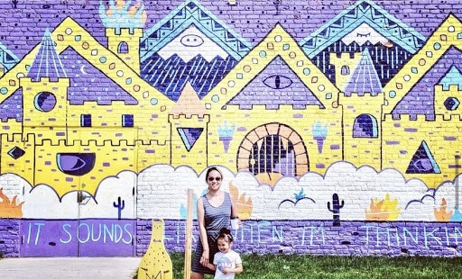 mother and daughter in front of mural