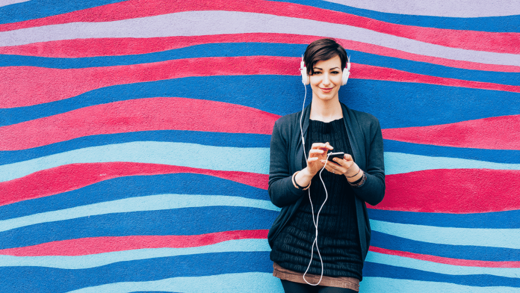 woman wearing headphones in front of blue and pink striped wall