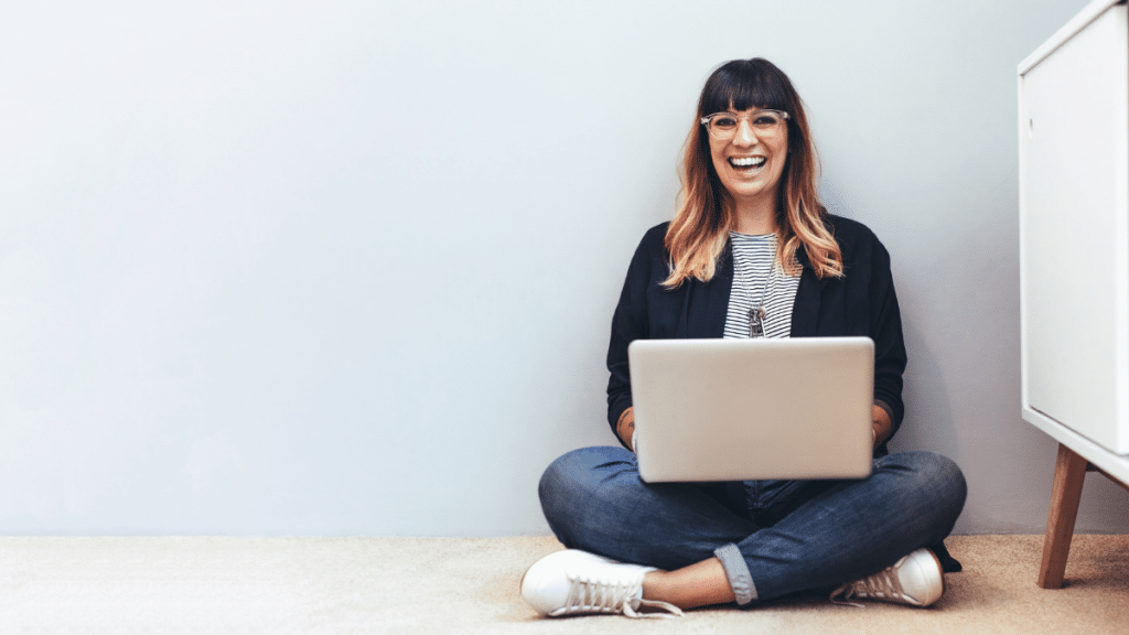 woman with brown hair and glasses sitting on the floor smiling with laptop
